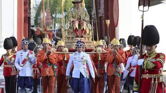 Der neu gekrönte thailändische König Maha Vajiralongkorn wird von seiner königlichen Garde auf einer Sänfte durch die Strassen der Hauptstadt Bangkok getragen.