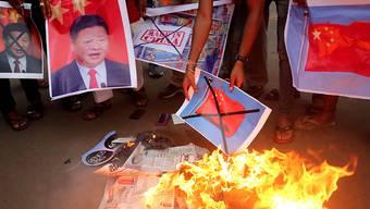 Proteste gegen den Grenzzwischenfall zwischen China und Indien: Nationalisten verbrennen in Bhopal Bilder chinesischer Flaggen und des chinesischen Präsidenten Xi Jinping.