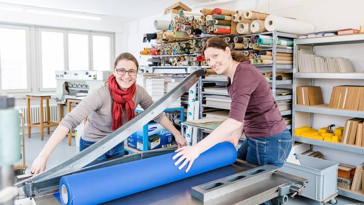 Die Buchbinderinnen Isabel Wey (links) und Petra Stäger helfen sich beim Papierschneiden in ihrer Buchbinderei.