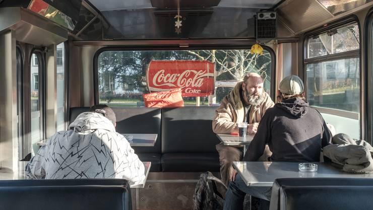 Drei Männer besuchen den Bus im Park auf dem Schlossplatz. Er steht auch an Festtagen offen.