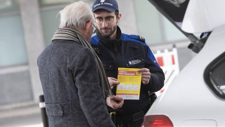 Ein Mitarbeiter der Bundeszollverwaltung verteilt an der schweizerisch-italienischen Grenze in Chiasso Broschüren über die Präventionskampagne des Bundesamtes für Gesundheit (BAG) gegen die Ausbreitung des Coronavirus COVID-19.