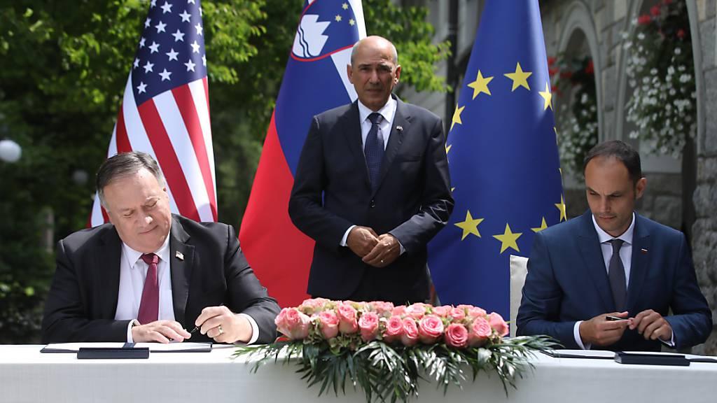 US-Außenminister Mike Pompeo (l) und sein slowenischer Amtskollege An·e Logar (r) unterzeichnen in Anwesenheit von Ministerpräsident Janez Jansa ein Abkommen zur 5-G-Sicherheit. Foto: Anze Malovrh/STA/dpa