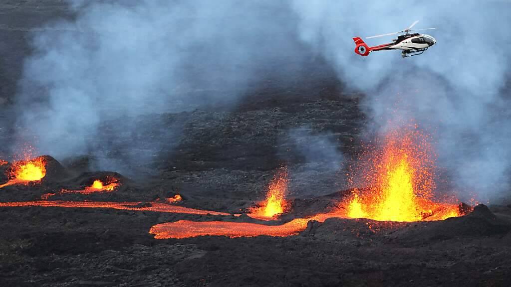 dpatopbilder - Ein Hubschrauber fliegt über dem ausbrechenden Vulkan Piton de la Fournaise auf der französischen Insel Reunion im Indischen Ozean. (Archivbild) Foto: Richard Bouhet/AFP/dpa