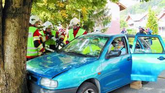 Präzis: Ein Rettungssanitäter versorgt das Opfer, während die Feuerwehr an der Carrosserie die Hydraulikschere ansetzt.