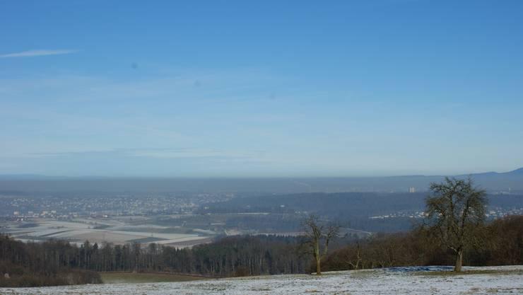 Minuspunkte: Die Luftqualität ist oft schlecht. Das Bild aus Pfeffingen zeigt den Smogstreifen, der im letzten Winter über Basels Agglomeration hing. (Bild: Andreas Maurer)