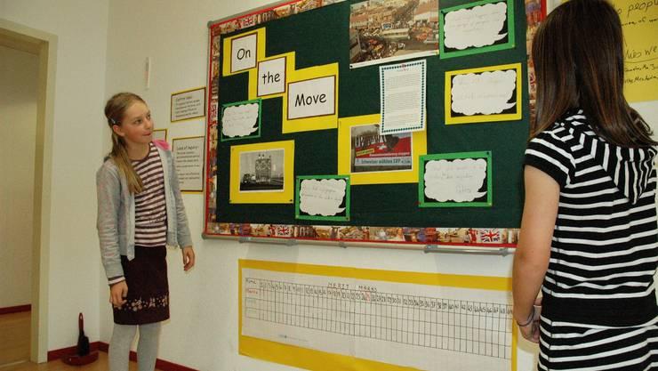 Zwei Schülerinnen erklären ihr Plakat zum Thema Migration.