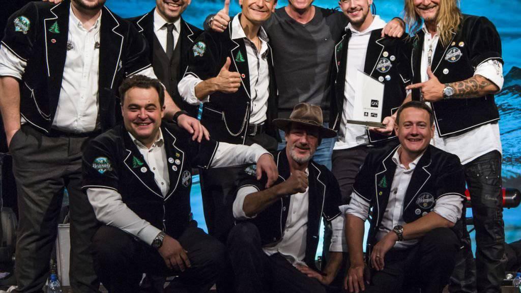 Heimweh nimmt aus den Händen von Andy Renggli, General Manager Schweiz GfK Entertainment (der ohne Chutteli) den «Nummer 1 Award der Offiziellen Schweizer Hitparade» entgegen. (Pressebild)
