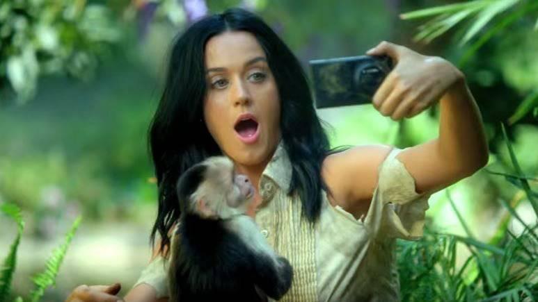 Katy Perry fotografiert sich mit einem Smartphone im Dschungel.