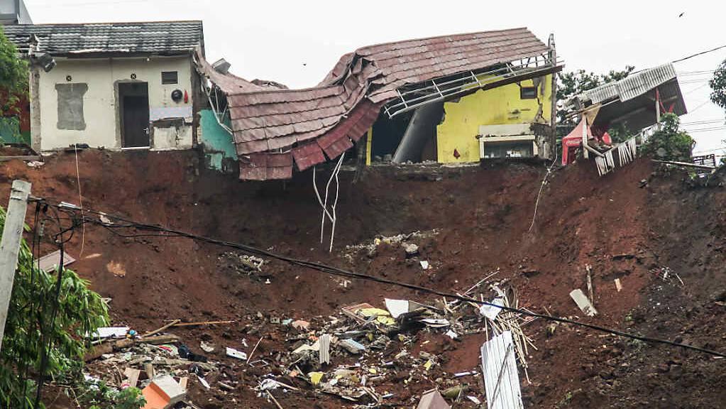 Ruinen eines Hauses hängen über einen Hang in Sumedang, Indonesien, an dem ein Erdrutsch heruntergegangen ist.