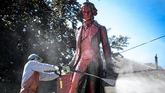 Ein Angestellter reinigte am Montagmorgen die Statue des umstrittenen Händlers David de Pury von der roten Farbe. De Pury lebte im 18. Jahrhundert.