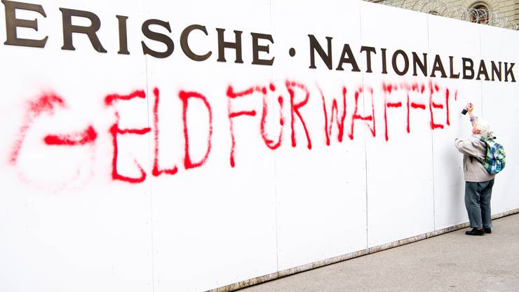 Zum Sammelstart besprayt in Bern eine Friedensaktivistin der Gsoa eine Baustellenwand der Schweizerischen Nationalbank.