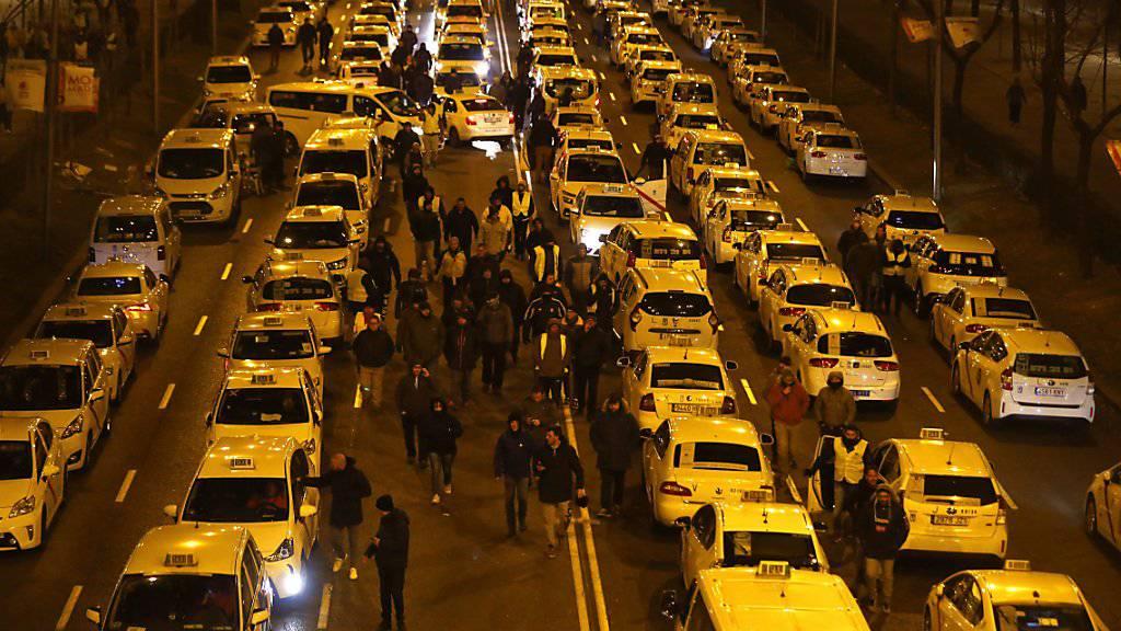 Aus Protest gegen Fahrdienste wie Uber blockierten Taxifahrer in Madrid mit ihren Fahrzeugen zentrale Strassen - nun hat die Polizei die Strassen geräumt.