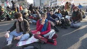 Des manifestant bloquent le Pont Chauderon en prenant le petit-dejeuner lors d'une manifestation en musique du groupe Extinction Rebellion en faveur du climat lundi 15 avril 2019 a Lausanne. (KEYSTONE/Laurent Gillieron)