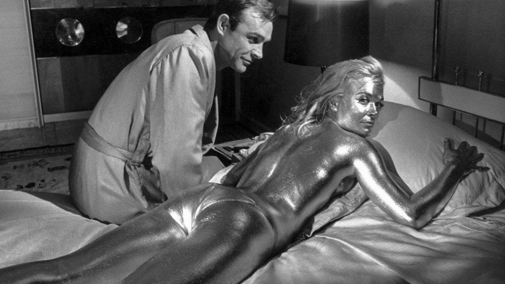 Sean Connery in der Rolle des James Bond und die vergoldete Shirley Eaton während den Dreharbeiten zu «Goldfinger» im Jahre 1964. Am Mittwoch ist dessen Regisseur Guy Hamilton mit 93 Jahren gestorben. (Archivbild)