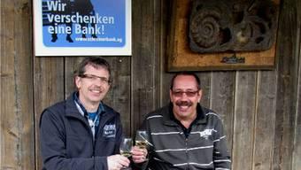 David Kläusler (links) und VEB-Präsident Peter Scheuble stossen beim Bergwerk Herznach auf die neuen Bänke beim Bahnhof der Stollenbahn an. – Foto: Ellen Schmid