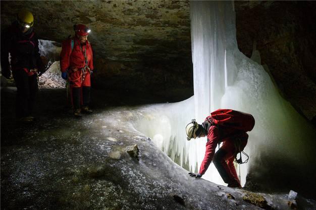 Die Höhlenforscher Eve Chédel (rechts) und Armin Behrend (Mitte) und der Journalist betrachten eine Eisformation, die durch Schmelzwasser entstanden ist.