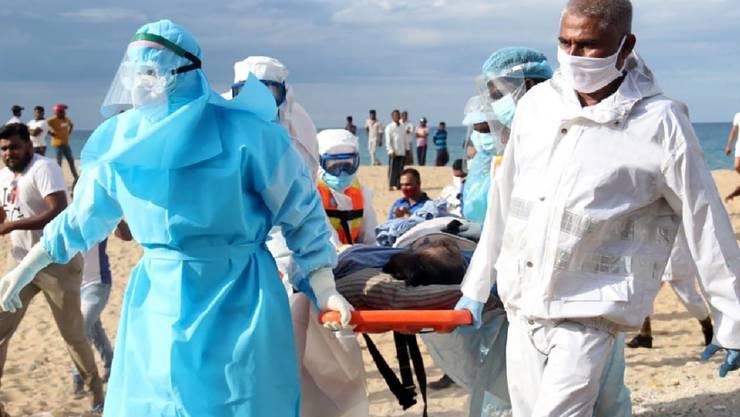 HANDOUT - Ein verletztes Besatzungsmitglied des Frachters «New Diamond» wird zu einem Krankenwagen getragen. Foto: Uncredited/Sri Lanka Navy/AP/dpa - ACHTUNG: Nur zur redaktionellen Verwendung im Zusammenhang mit der aktuellen Berichterstattung und nur mit vollständiger Nennung des vorstehenden Credits