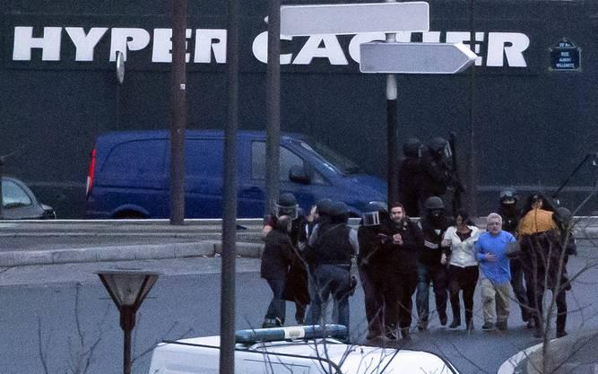 Paris: Polizeikräfte nehmen die geretteten Geiseln aus dem Supermarkt in Empfang.