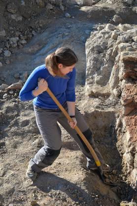 Grabungsleiterin Simone Mayer legt auf der Vorderseite den Kanal frei - Schwerstarbeit