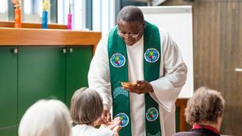 Religiöse Gemeinschaft, die über die Grenzen der Kulturen reicht: Pfarrer Willy Mayunda mit einer Altersheimbewohnerin.