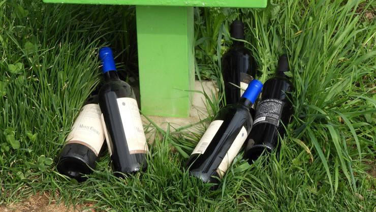 Littering der etwas anderen Art: ungeöffnete Weinflaschen im Gras.
