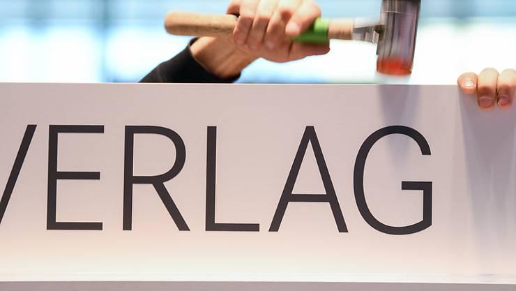 """ARCHIV - Am Stand des at Verlags wird ein Schild mit der Aufschrift """"Verlag"""" auf einem Regal befestigt. Die Frankfurter Buchmesse wird virtueller und will Stellen streichen. Foto: Arne Dedert/dpa"""