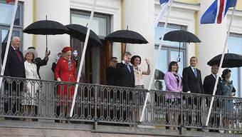 Trotz Regen in Feierlaune: Der finnische Präsident Sauli Niinistö, seine Frau Jenni Haukio (Mitte) und ihre hochrangigen Gäste.