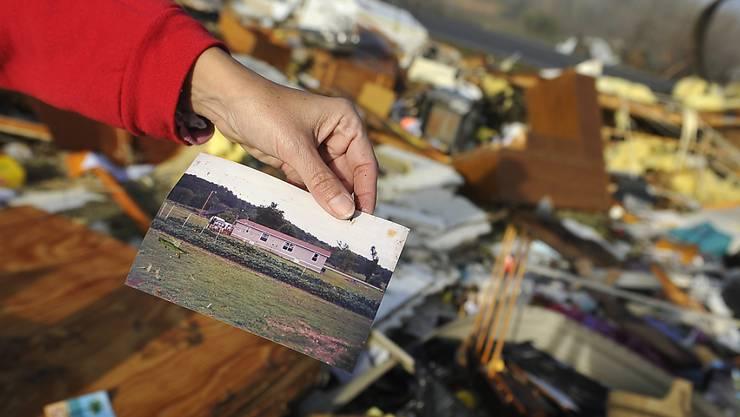 Vor den Trümmern eines Hauses in Lutts, Tennessee, zeigt eine Frau ein Foto des Gebäudes vor dem Durchzug des Tornados.