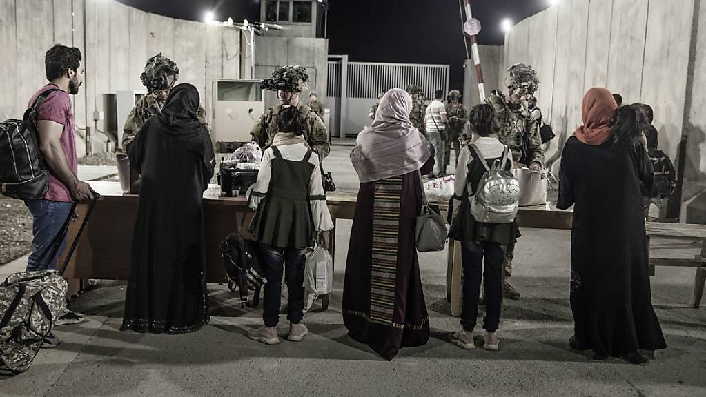 Soldaten der 82. Luftlandedivision der US-Army helfen Menschen während der Evakuierung auf dem Flughafen Kabul.