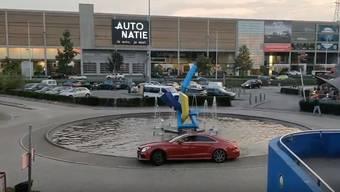 Im Hintergrund passend: ein Autohändler – der allerdings keine Mercedes verkauft.