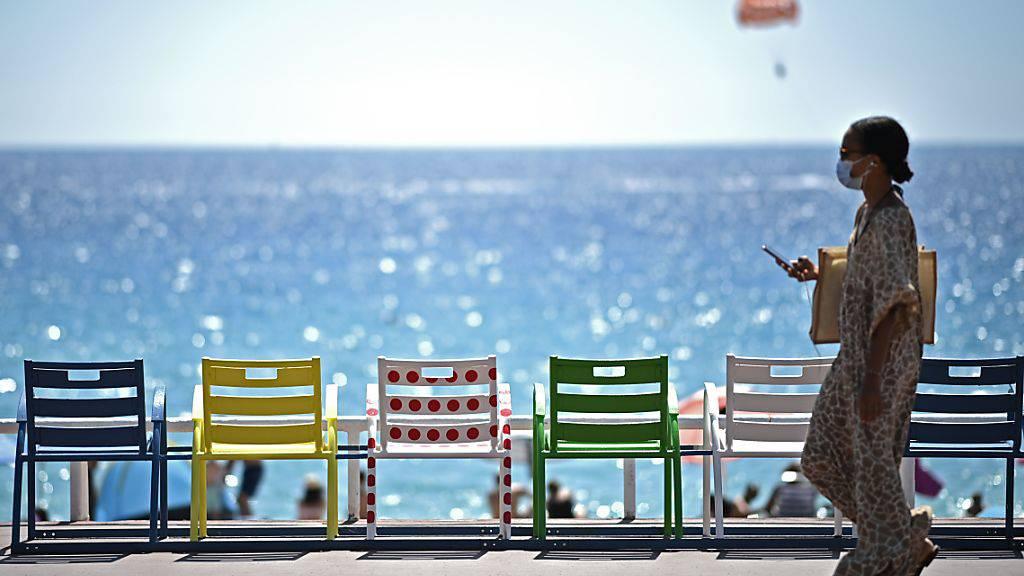 Eine Frau geht auf der Strandpromenade an der französischen Riviera an Stühlen vorbei. Foto: Anne-Christine Poujoulat/AFP/dpa
