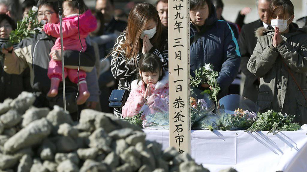 Angehörige gedenken der Opfer des Erdbebens und des Tsunamis vom  11. März 2011.