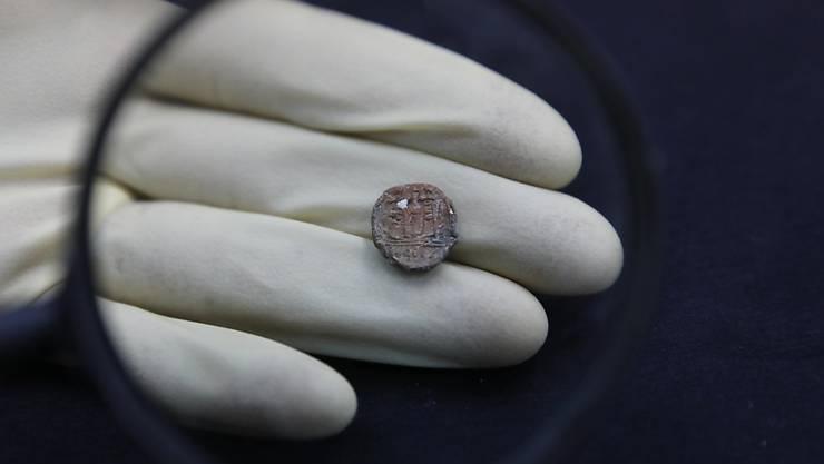 Eine Archäologin zeigt das Tonstück, das rund 2700 Jahre alt ist.
