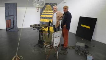 Gilbert Peyre (l.) und Behrouz Varghaiyan stellen ab dem kommenden Samstag gemeinsam im Laufenburger Rehmann-Museum aus. Peyres bewegliche Installation mit Tisch und Weinflasche heisst «Deux Amis» und ist Namensgeberin der Ausstellung. Die Bilder im Hintergrund sind von Varghaiyan. Marc Fischer