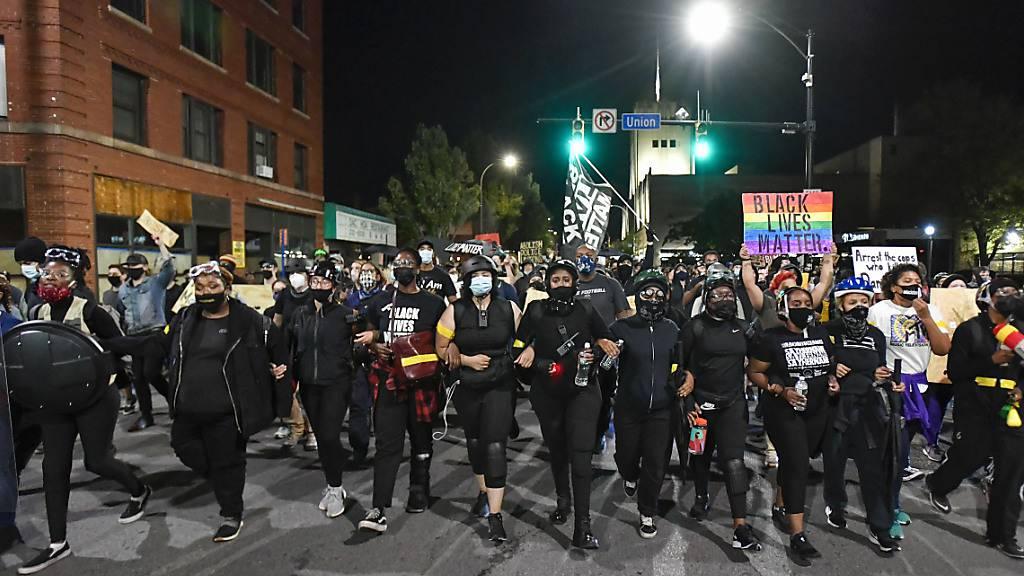 Demonstranten gehen untergehakt durch die Stadt. Ihr Protest richtet sich gegen Polizeigewalt und Rassismus. Nach dem Tod des Schwarzen Daniel Prude bei einem Polizeieinsatz im März waren mehrere Beamte von Dienst suspendiert worden. Foto: Adrian Kraus/FR171451 AP/dpa