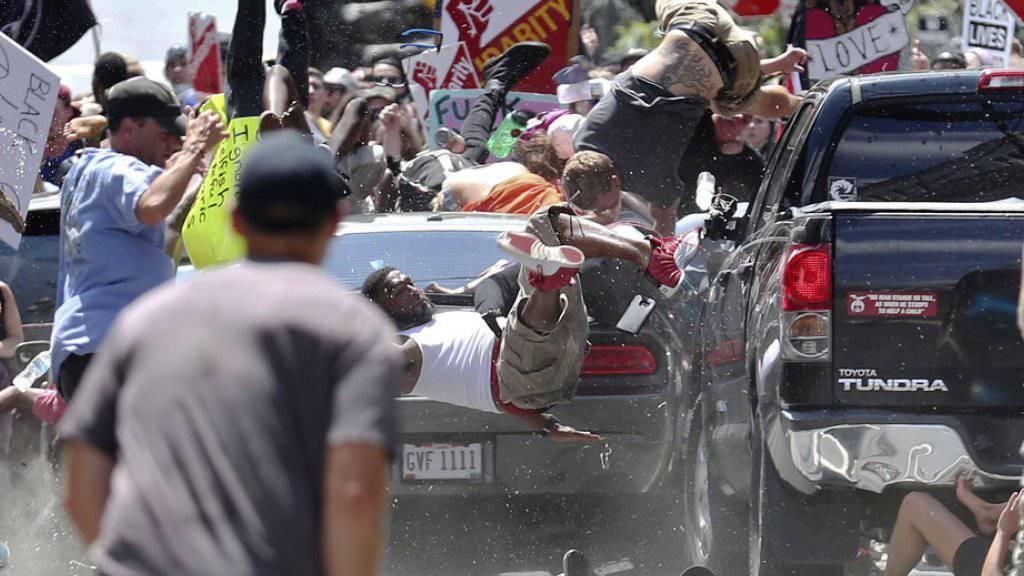Menschen fliegen durch die Luft, als das Auto in die Menge fährt.