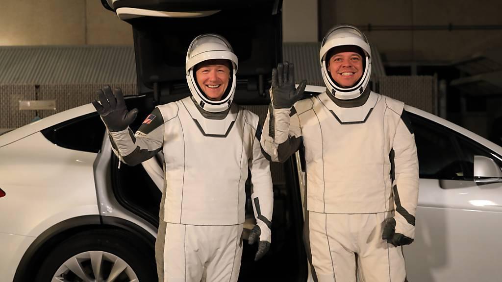 Die Astronauten Doug Hurley (links) und Bob Behnken vor einem Tesla-Elektroauto im Kennedy Space Center in Florida. (Archivbild)