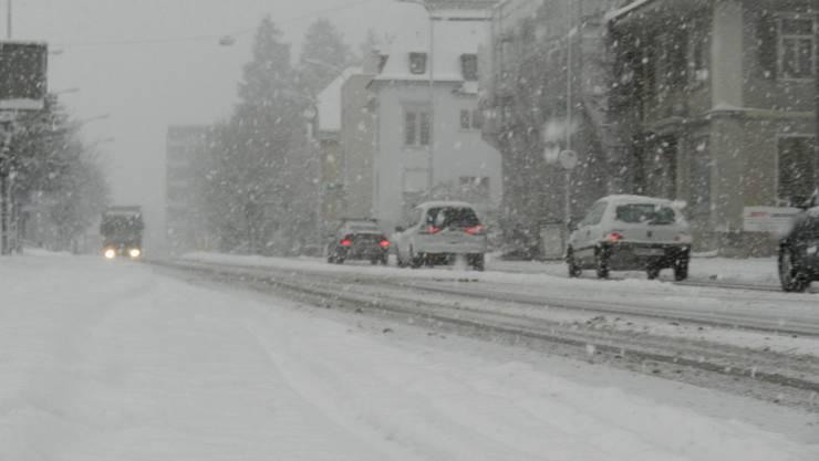Autos fahren im Schneegestöber auf der Zuchwilerstrasse in Solothurn.