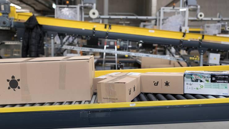 Rollbänder befördern die verpackten und versandbereiten Bestellungen zu den Paketrollbehältern der Schweizerischen Post.