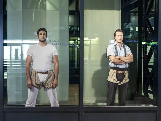 Zwei Schwinger in Lebensgrösse «kleben» am Schaufenster eines Geschäfts in Zug.