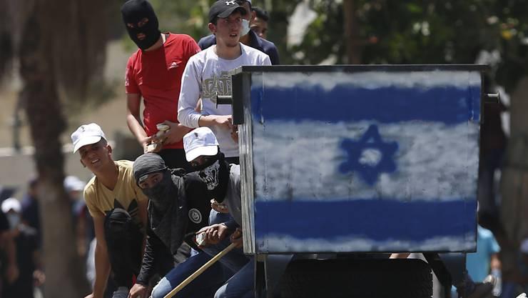 Palästinensische Demonstranten schleudern Steine auf israelische Truppen während eines Protests in Kufr Qaddum gegen Israels Plan, Teile des Westjordanlandes zu annektieren. Foto: Majdi Mohammed/AP/dpa