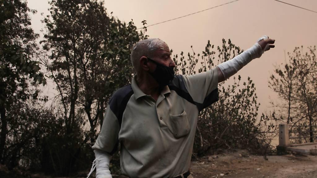 Ein Mann flieht aus einem Dorf in der Nähe von Tizi Ouzou, etwa 100 km östlich von Algier. Foto: Fateh Guidoum/AP/dpa