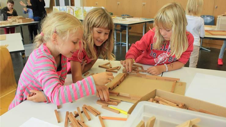 Statik-Übung: Drei Mädchen versuchen, ein möglichst stabiles Haus zu bauen.