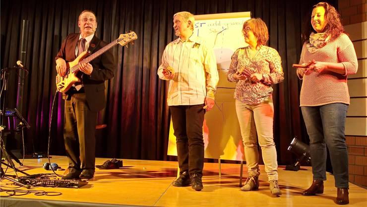Drei Personen aus dem Publikum begleiten Dani Ziegler mit Perkussionsinstrumenten.