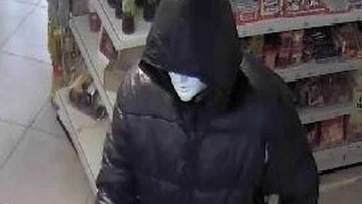 Der Mann trug eine weisse Maske, als er den Tankstellenshop überfiel. (Archiv)