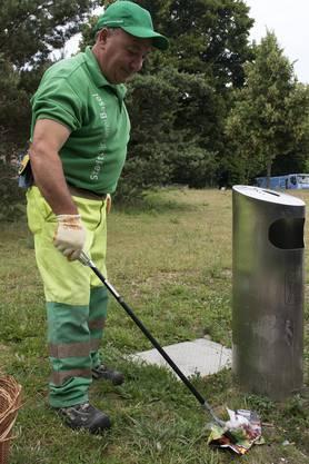 Ein Mitarbeiter der Stadtgärtnerei sammelt liegen gelassenen Abfall ein im St. Johanns-Park in Basel.