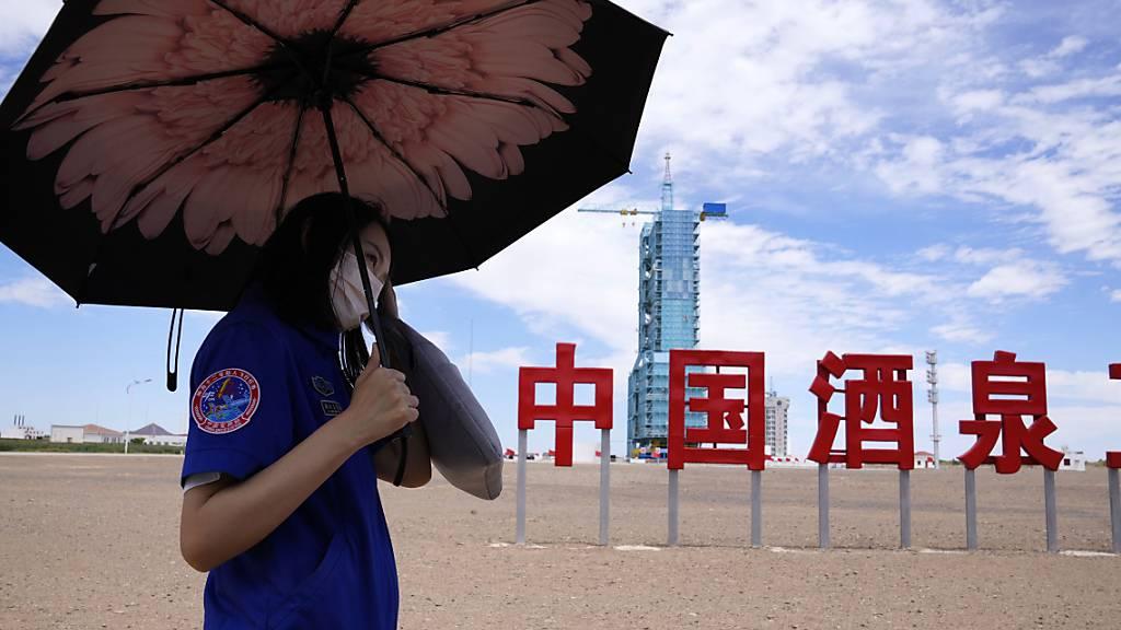 Ein Arbeiter hält einen Regenschirm in der Nähe des Raumschiffs Shenzhou-12, das auf der Startrampe mit den chinesischen Schriftzeichen «China Jiuquan Satellite Launch Center» steht. Foto: Ng Han Guan/AP/dpa