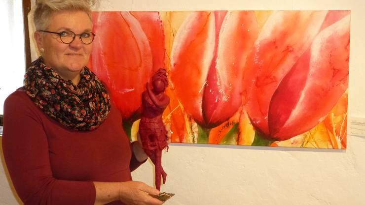 """Rosa Gasche mit einer ihrer Figuren vor dem Bild """"Frühlings Liebe""""."""