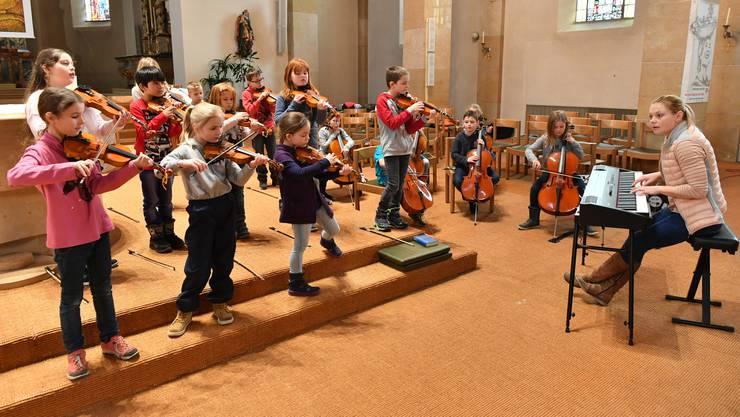Musiklehrerin Katharine Rüegg und ihre Streicherklasse üben hoch konzentriert für das Konzert in der katholischen Kirche in Mümliswil.