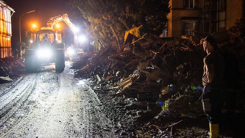 Trümmerteile werden von einem Bagger mit Anhänger im Landkreis Ahrweiler in Rheinland-Pfalz verladen. Nach der Hochwasserkatastrophe im Westen Deutschlands ist die Zahl der Toten auf mehr als 130 gestiegen. Foto: Lino Mirgeler/dpa